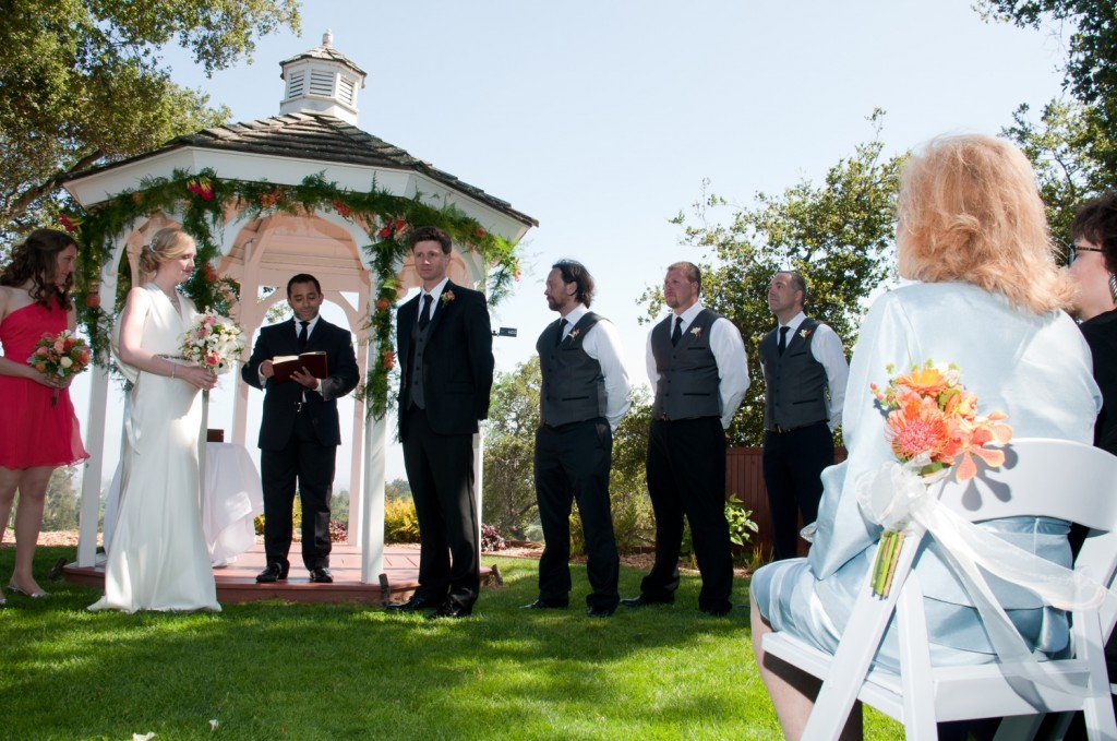 Barbara sits in the foreground, watching her son get married.