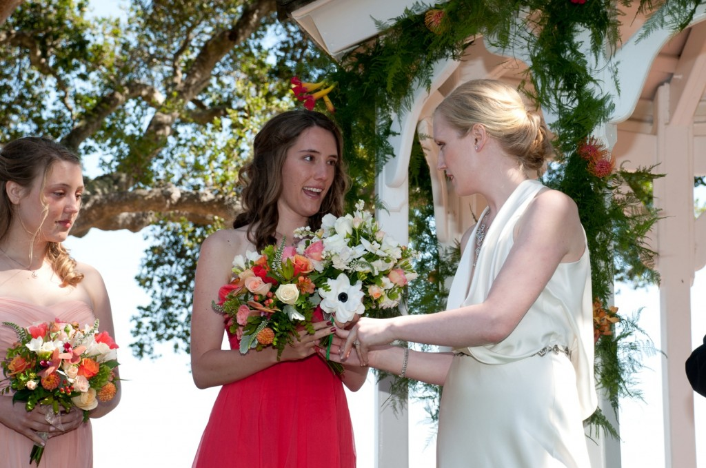 Elizabeth passes her bouquet to Christine for safe keeping.