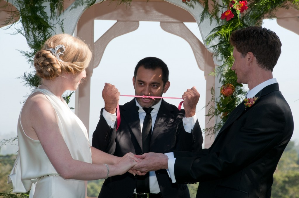 Christian ties the two cut pieces of ribbon into a knot.